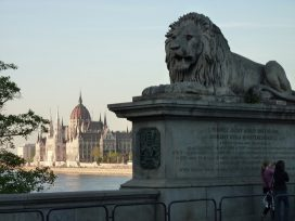 A lion monument in front of the Hungarian Parliament